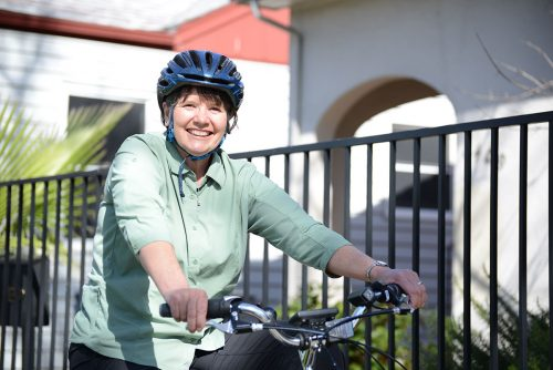 An image of Sister Libby smiling on a bike