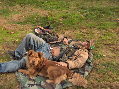 An image of a homeless man and a dog on grass
