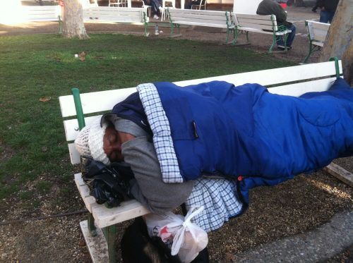 An image of a homeless man sleeping on a bench