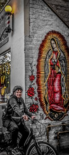 An image of Sister Libby on a bike in front of a wall with a Guadelupe picture