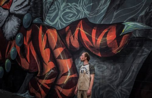 An image of a man standing in front of a mural