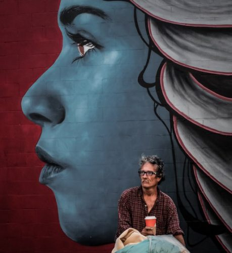 An image of a man sitting in front a muraled wall
