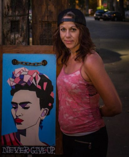 An image of a woman next to a paining of Frida Kalo