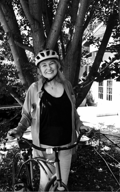 An image of a woman smiling next to a bike